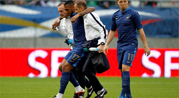 France's Yann M'Vila leaves the field after being injured during a friendly against Serbia on May 31