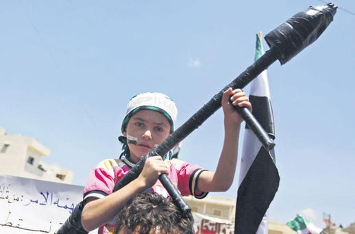 A Syrian boy carries a toy rocket-launcher during an anti-Bashar al-Assad protest after prayers on the outskirts of Idlib yesterday