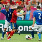 Spain's Cesc Fabregas (C) is challenged by Italy's Thiago Motta (L) and Christian Maggio. Photo: Reuters