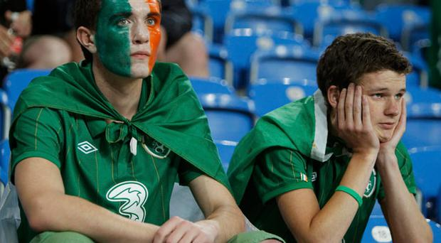 Ireland fans sit dejected in the stands after their teams defeat to Croatia