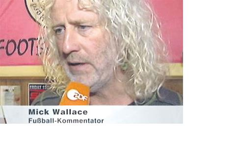 TD Mick Wallace is described as a 'football commentator' in a brief appearance on a German television channel yesterday.