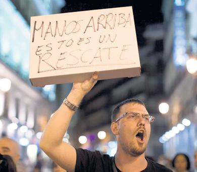A protester carries a sign saying 'Hands up, this is a rescue', during a demonstration against the bailout in Madrid at the weekend.