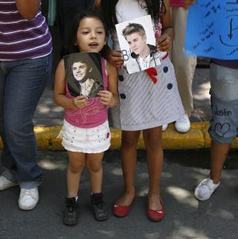 Fans hold images of pop starJustin Bieber in Mexico City's main plaza, the Zocalo (AP/Marco Ugarte)