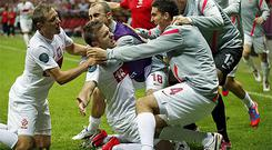 Jakub Blaszczykowski is mobbed by his Polish team mates after his second half equaliser