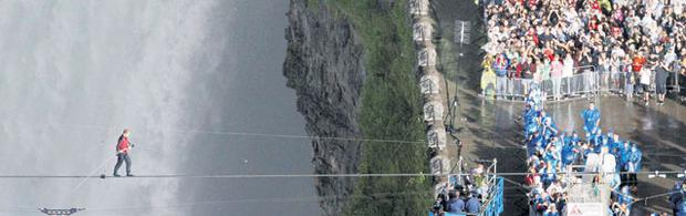OUT FOR A STROLL: Nik Wallenda, of famous acrobatic family The Flying Wallendas, tightrope-walks across Niagara Falls as spectators look on. Photo: Mark Blinch