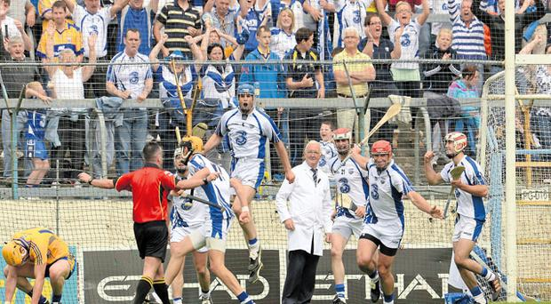 Waterford players and supporters celebrate as referee James McGrath signals the end of the game in Thurles yesterday