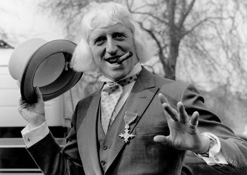 British radio disc jockey, television broadcaster and charity fundraiser Sir Jimmy Savile sporting his OBE after his investiture at Buckingham Palace, London. Photo: Getty Images