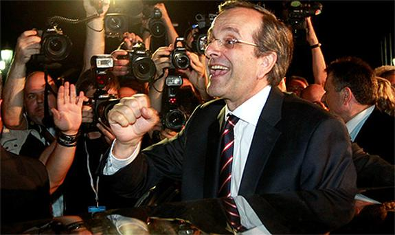 Leader of conservative New Democracy party Antonis Samaras is cheered by supporters after his statement on the election results in Athens