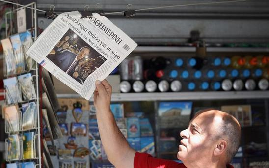 A man reads a newspaper on the street reporting Sunday's general election as party leaders meet to attempt to form a coalition government on Monday. Photo: Getty Images