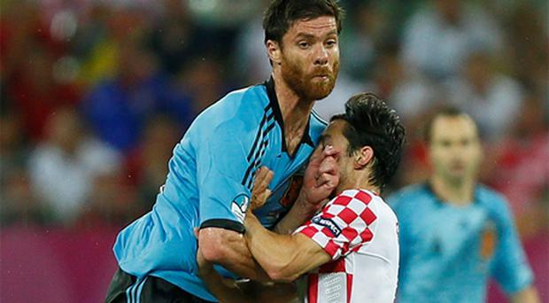 Spain's Xabi Alonso challenges Croatia's Danijel Pranjic (R) during their Group C match at the PGE Arena in Gdansk