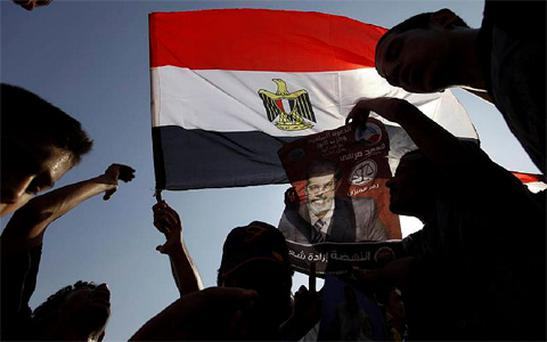 gyptian supporters of Muslim brotherhood candidate Mohammed Morsi hold a poster with Arabic that reads,