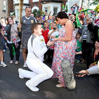 David State stops midway through his torch relay leg between Marske-by-the-Sea and Loftus to propose to his girlfriend (Locog/PA)