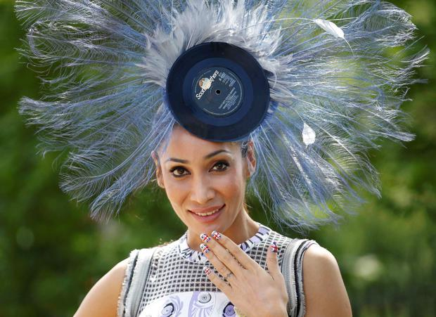 A race goer poses for photographs on the first day of the Royal Ascot, southwest of London, June 19, 2012. REUTERS/Andrew Winning (BRITAIN - Tags: SPORT HORSE RACING SOCIETY)
