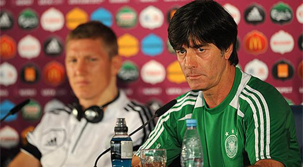 German manager Joachim Low and Bastien Schweinsteiger, left, speak to reporters ahead of tonight's clash with Greece