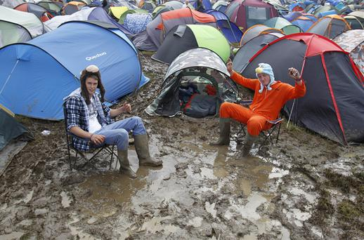 Revellers wallow in the mud at the campsite at the Isle of Wight festival. Photo: PA