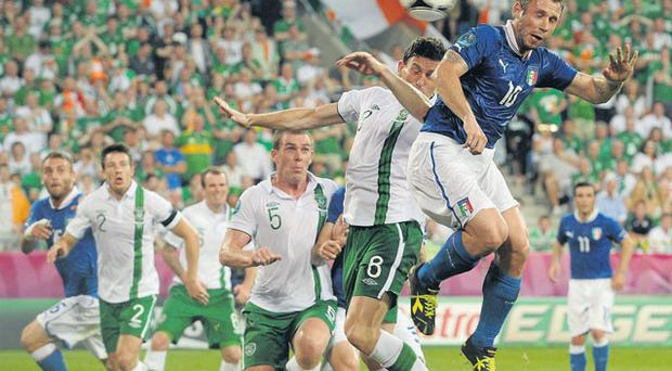 Antonio Cassano outjumps Keith Andrews to score for Italy against Ireland last Monday