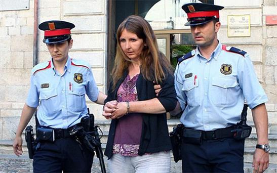 Lianne Smith is led away from the Provincial Court in Girona, north-east Spain. She was found guilty of their 'abominable' murders