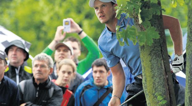 England's Danny Willett watches his shot from behind a tree on his way to winning the BMW International in Munich