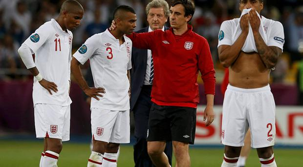 Gary Neville (2nd R) comforts England's Ashley Cole (2nd L) and Ashley Young (L) after their missed penalties resulted in England's ezxit from Euro 2012. Photo: Reuters