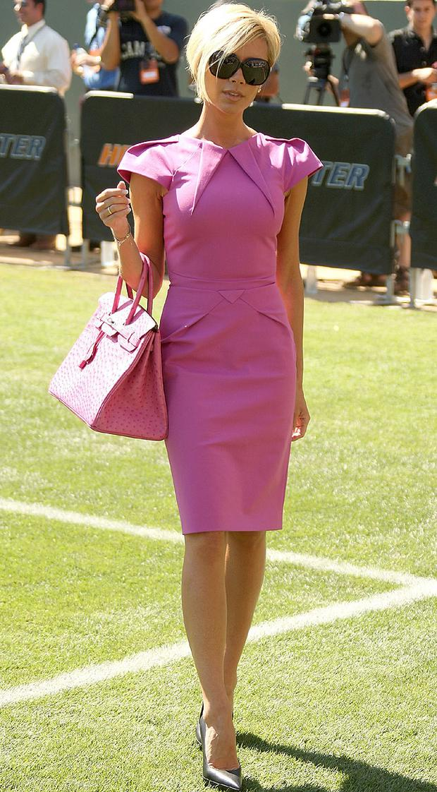 Victoria wearing a pink Roland Mouret dress accessorised with one of her reported 100 Hermes handbags. Photo: Getty Images