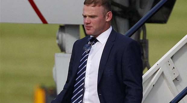Wayne Rooney makes his way off the team plane as members of the England team arrive at Manchester Airport. Photo: PA
