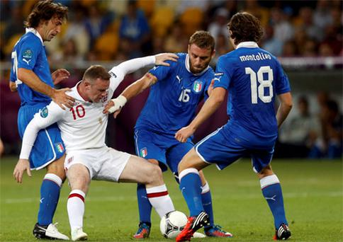 Wayne Rooney surrounded during the game against Italy