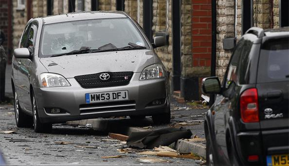 A damaged car sits amongst debris on Oak Street close to the scene of a suspected gas blast in Buckley Street in the Shaw area of Oldham. Photo: PA