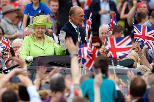 Queen Elizabeth waves to members of the public as she and her husband Prince Philip drive through the Stormont estate during a Diamond Jubilee event in Belfast. Photo: Reuters