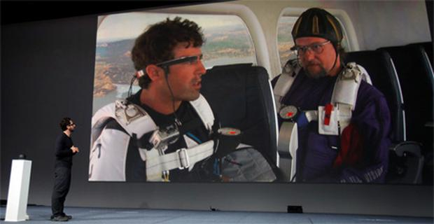 Sergey Brin, CEO and co-founder of Google, watches a live broadcast as two parachutists prepare to parachute onto Mascone City wearing Google Glass