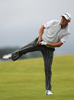 Mark Murphy stands on one leg as he watches his second shot on the 8th hole