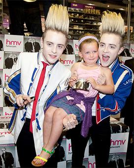 Jedward Fan Niamh LAmon (4) from Lucan gets a copy of Jedward's new album 'Young Love' signed by the duo in HMV Dundrum, Dublin