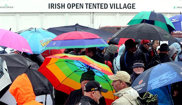 People shelter from the rain as play is suspended due to bad weather during day one of the Irish Open