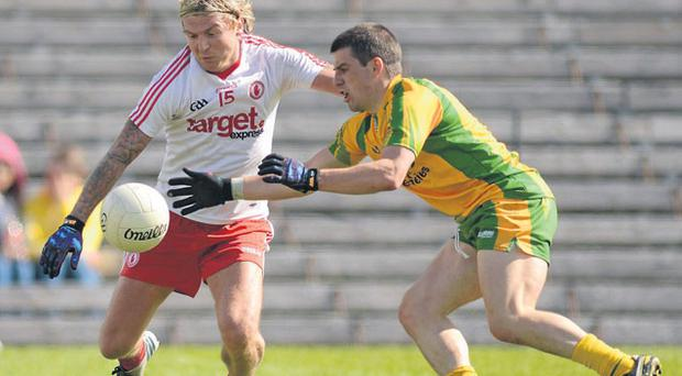 Tyrone's Owen Mulligan battles for the ball with Paddy McGrath of Donegal in Clones last night. Photo: Oliver McVeigh.