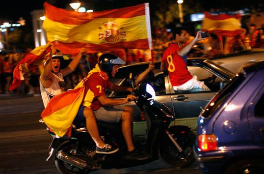Fans of Spain wave Spanish flags as they celebrate in their vehicles after Spain's victory over Italy. Photo: Reuters