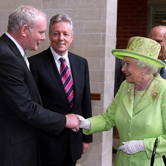 Queen Elizabeth shakes hands with Northern Ireland's Deputy First Minister Martin McGuinness watched by First Minister Peter Robinson