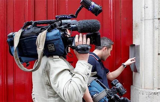 Journalists press a buzzer at the entrance of a building which houses the new offices of former French President Nicolas Sarkozy in Paris, France. Photo: Reuters