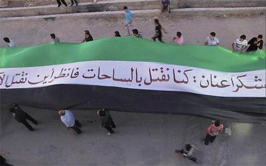Anti-government demonstrators in Kafr Susa, near Damascus, Syria. The partial translation of the Arabic reads,