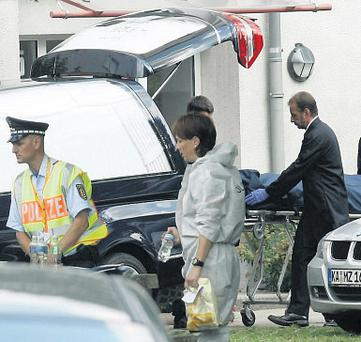A body is put into a funeral car at the scene of the shootings at a flat in Karlsruhe, Germany, yesterday