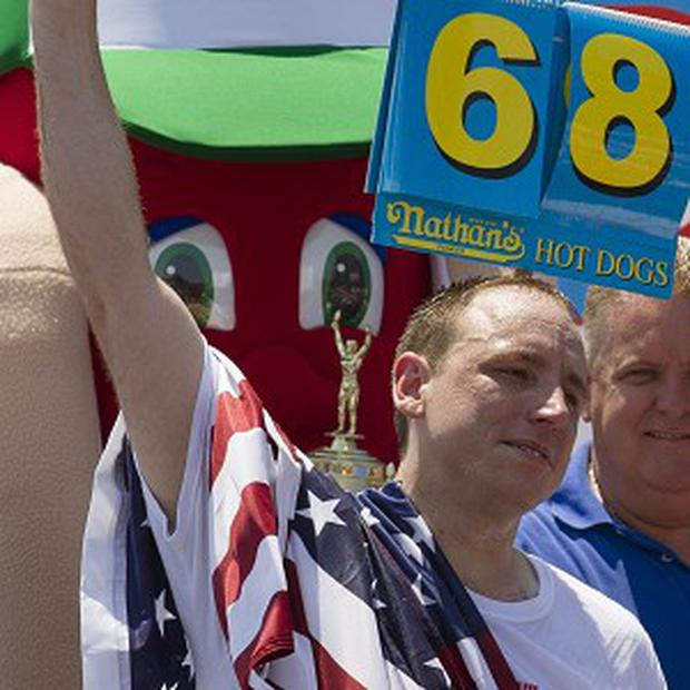Five-time reigning champion Joey Chestnut celebrates after he wins his sixth Nathan's Famous Hot Dog Eating World Championship (AP)