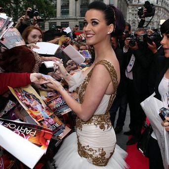 Katy Perry signs autographs for fans as she arrives for the premiere of Katy Perry Part Of Me 3D