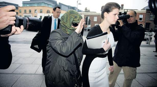 FRAUDSTER: Adam Clayton's former PA Carol Hawkins (face covered) arriving at court before she was jailed for seven years