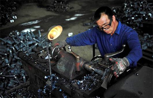 A worker produces automobile components at a car parts plant in Shenyang, Liaoning province. Photo: Reuters