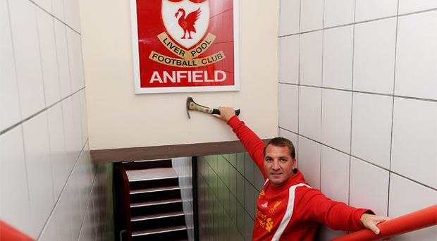 Liverpool manager Brendan Rodgers under the original 'This Is Anfield' sign after it was remounted at Anfield yesterday