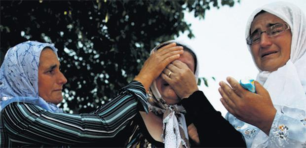 Bosnian women cry as newly identified Srebrenica massacre victims leave a morgue yesterday.