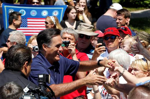 S Republican presidential candidate and former Massachusetts Governor Mitt Romney shakes hands with people along the parade route as he takes part in the Wolfeboro Fourth of July Parade in Wolfeboro, New Hampshire