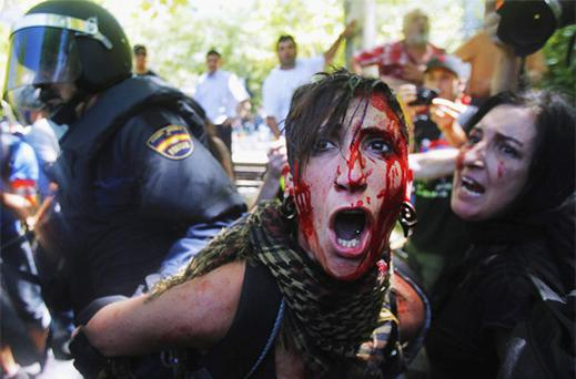 A demonstrator bleeds as she is detained by the riot police during a coal miners's march to the Minister of Industry building in Madrid yesterday.