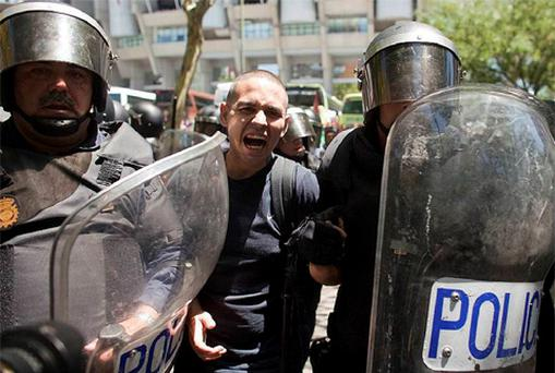 A protester is detained by riot police during clashes between supporters of Spanish coal miners and riot police as they ended a