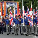 Orangemen make their way through the Nationalist Ardoyne area of north Belfast
