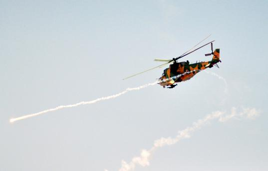 Syrian military helicopter takes part in a live ammunitions exercise in an undisclosed location on July 10, 2012