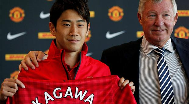 Manchester United's new signing Shinji Kagawa of Japan holds up a team shirt with manager Alex Ferguson. Photo: Reuters
